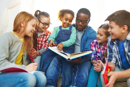 children learning: Little pupils and their teacher reading book together