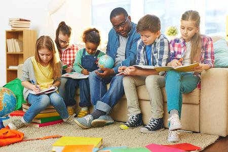ni�o escuela: Los ni�os peque�os que escriben en sus cuadernos en la lecci�n Foto de archivo