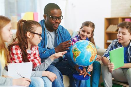 Grupo de niños en edad preescolar estudiar nuestro planeta en el globo