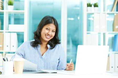 Fröhlich Geschäftsfrau, die Kamera, während am Arbeitsplatz sitzen
