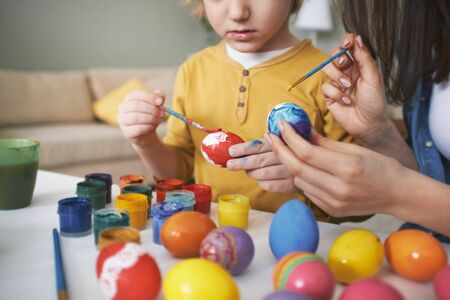 handmade: Mother and son painting Easter eggs with gouache Stock Photo