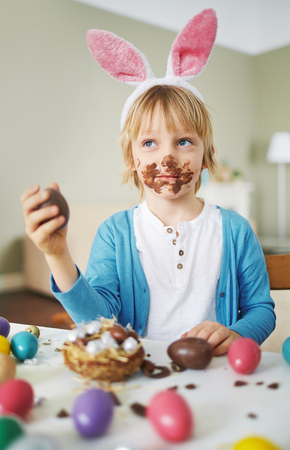 chocolate dessert: Cute boy with rabbit ears eating chocolate Easter eggs
