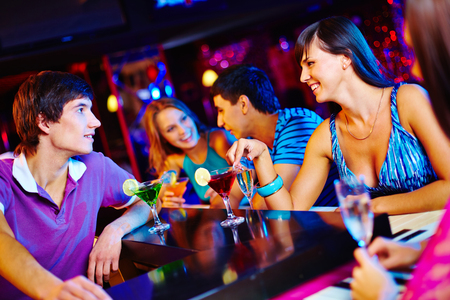 Young man and woman talking at nightclub photo