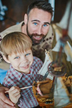 adult toys: Little boy and his father painting toy ship at leisure Stock Photo
