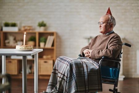 hombre solitario: El hombre mayor en silla de ruedas que tiene cumpleaños Foto de archivo