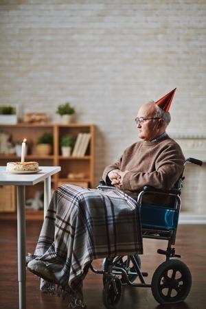 elderly man: Senior man on wheelchair celebrating his birthday on his own