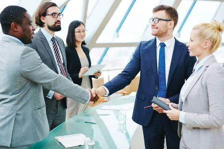 handshaking: Confident businessmen handshaking with colleagues near by