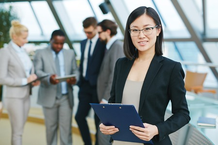 confident woman: Pretty Asian businesswoman looking at camera in working environment