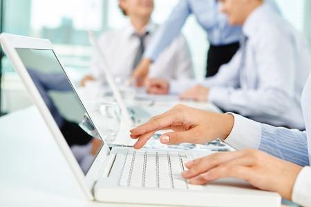 mecanografía: mano del hombre escribiendo en la computadora portátil en el entorno de trabajo Foto de archivo