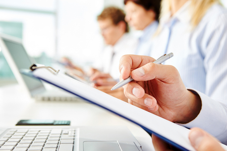 clipboard: Human hand with pen over clipboard with business document Stock Photo