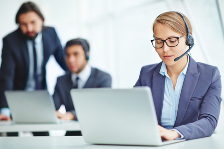 technology career: Busy operator with headset typing on laptop Stock Photo