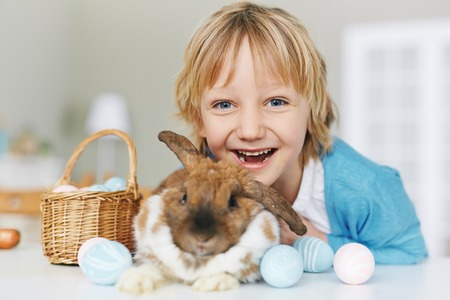 boy smiling: Laughing kid with cute Easter rabbit looking at camera Stock Photo