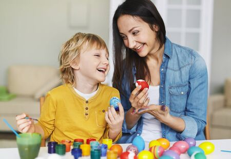 beautiful boy: Young woman and little boy painting Easter eggs together Stock Photo