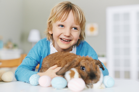 child laughing: Laughing boy with cute Easter rabbit Stock Photo