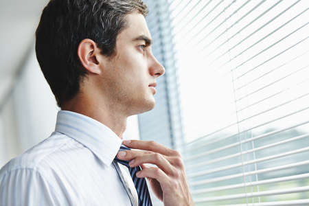 looking through window: Young businessman looking through window