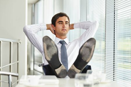 young businessman: Relaxed businessman sitting in office