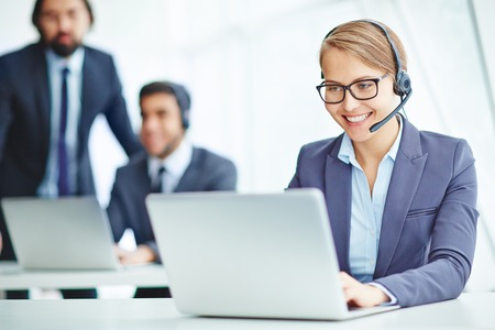 telephony: Pretty operator with headset consulting clients online Stock Photo