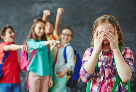 mockery: Schoolgirl crying on background of teasing classmates Stock Photo