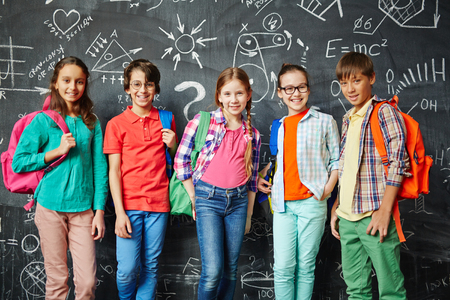 Happy pupils with backpacks standing against blackboard