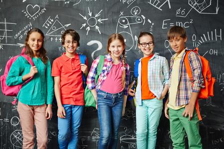 Szczęśliwi uczniowie z plecakami stojących przed tablicą
