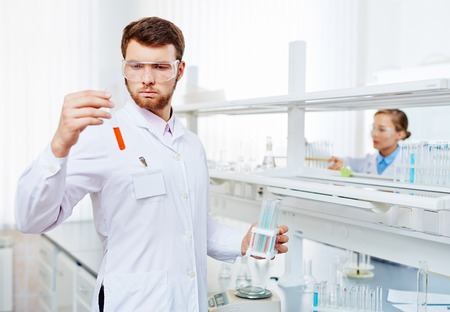 Young chemist looking at fluid substance in flask Stock Photo