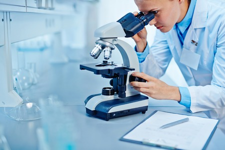scrutinize: Young scientist studying new virus in microscope Stock Photo