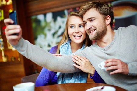 amorous: Amorous young couple making selfie in cafe