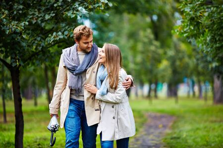 walk in: Happy young couple taking walk in park