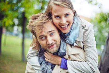 amorous woman: Ecstatic couple looking at camera outdoors Stock Photo