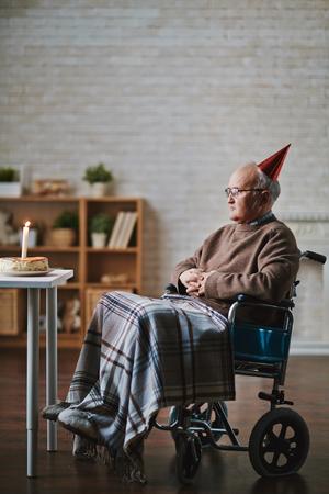 誕生日ケーキでテーブルの前に座っている車椅子の年配の男性 写真素材