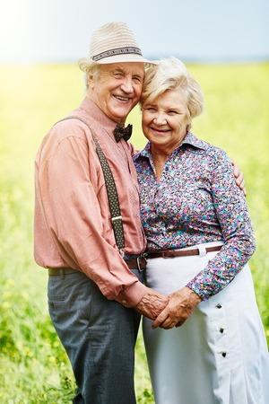 couples hug: Affectionate seniors looking at camera while enjoying summer day