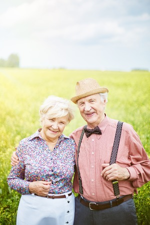 couples hug: Smiling senior couple looking at camera on summer day