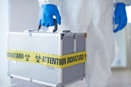 protective wear: Medical case with biohazard held by man in protective wear