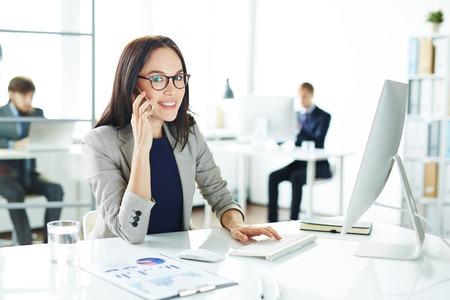 secretaria: Secretaria bonita que mira la cámara mientras se habla por teléfono celular