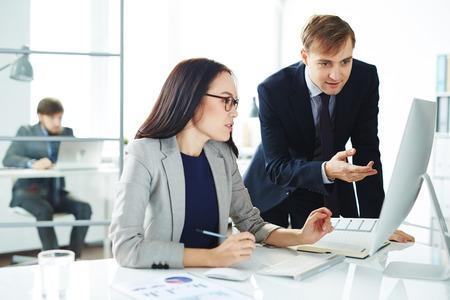 secretaria: Joven secretaria que discute los planes de trabajo con su jefe