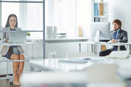 executive women: Two young managers doing their routine work in office Stock Photo