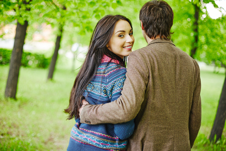 amorous woman: Back view of young man embracing happy girlfriend during walk in park