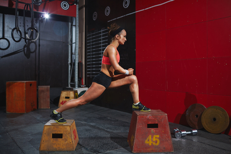 activewear: Young woman in active-wear training on jump-boxes in gym Stock Photo