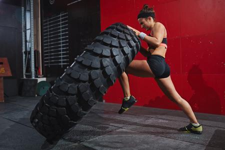 Mulher ativa no sportswear lançando pneu no ginásio Foto de archivo