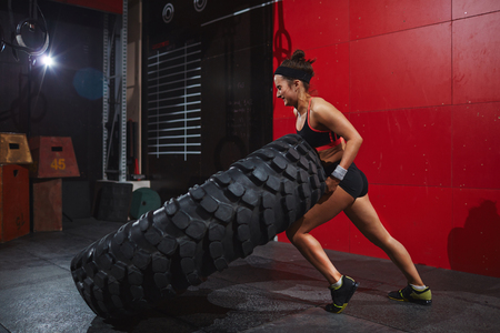 fit: Active and strong woman flipping tyre with help of arms and knee