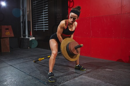 athletic wear: Strong young woman with heavy barbell training in gym