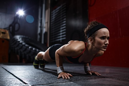 Fit woman doing push-ups in gym Stock Photo