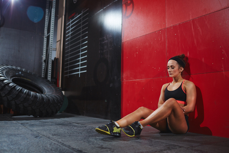 activewear: Fit woman in active-wear sitting on the floor against wall in gym Stock Photo