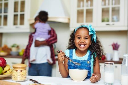 comiendo cereal: copos de maíz mañana muchacha que come afroamericanos felices