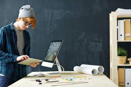 hombres jovenes: El diseñador joven con touchpad mirando a través de los datos por el lugar de trabajo Foto de archivo