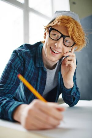 architect drawing: Handsome young architect speaking on the phone while drawing sketch