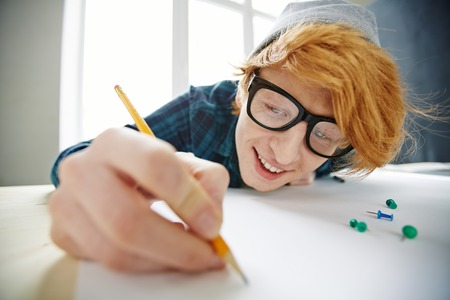 architect drawing: Happy young architect in eyeglasses drawing sketch Stock Photo