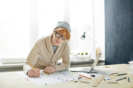 architect drawing: Confident architect drawing sketch and looking at camera in office Stock Photo