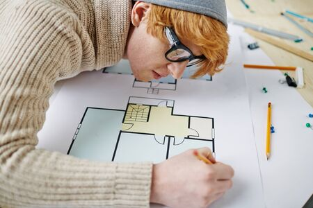 architect drawing: Contemporary architect in casual-wear drawing sketch Stock Photo