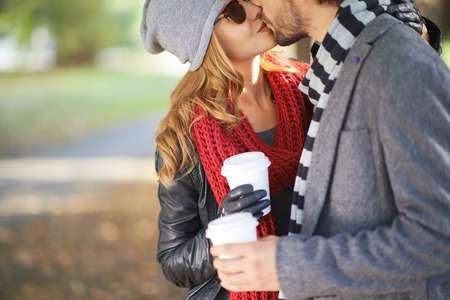 romantic man: Young couple with plastic glasses kissing outdoors